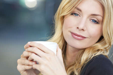 A beautiful smiling young woman with blond hair and blue eyes drinking coffee or tea from a white cupの写真素材