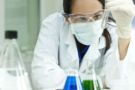 A female medical or scientific researcher or woman doctor looking at a test tube of clear solution in a laboratory with flasks in the foreground.