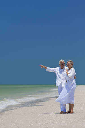 Happy senior man and woman couple together looking out to sea on a deserted tropical beach with bright clear blue sky, the man is pointing to the horizon