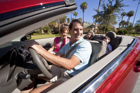 Man and woman parents and two children having fun driving in a red convertible car in sunshine
