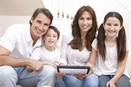 An attractive happy, family of mother, father, son and daughter sitting on a sofa at home having fun using a tablet computer