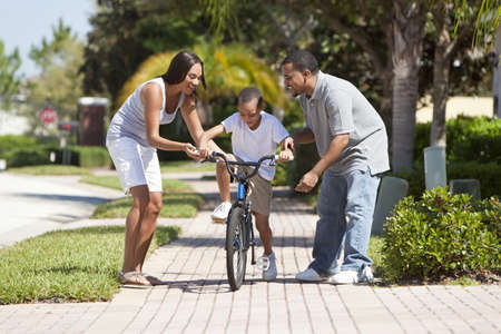 Photo pour A young African American family with boy child riding his bicycle and his happy excited parents encouraging him. - image libre de droit