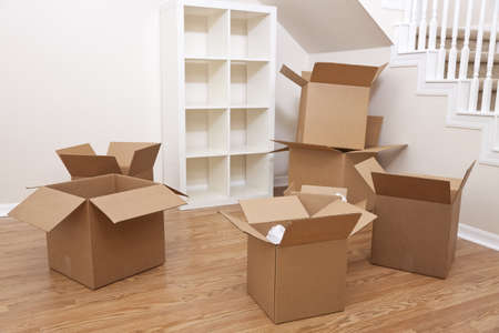 Empty room full of cardboard boxes for moving into a new home.