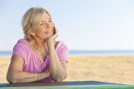 Photo for An attractive elegant and happy senior woman sitting outside out a table and thinking, behind her is a beach and the sea - Royalty Free Image