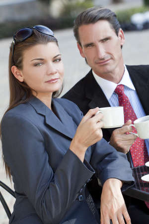 A beautiful and sophisticated young woman having coffee at a modern city cafe table with her friend a smart dressed businessman