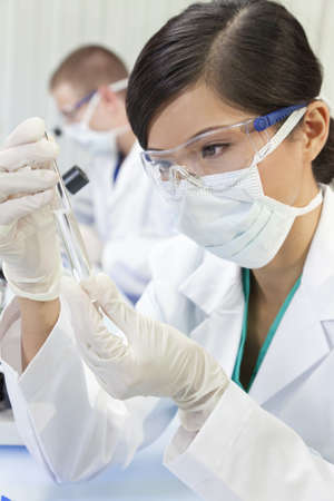 A Chinese Asian female medical or scientific researcher or doctor using looking at a test tube of clear liquid in a laboratory with her colleague out of focus behind her.