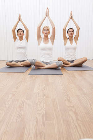 An interracial group of three beautiful young women sitting cross legged in a yoga position at a gymの写真素材