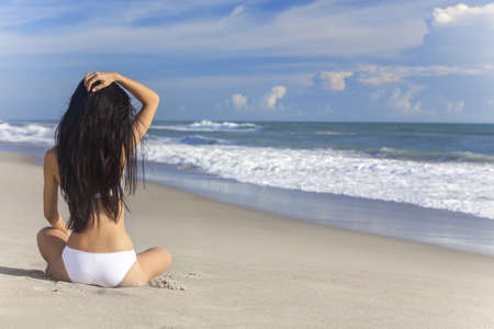 A sexy young brunette woman or girl wearing a white bikini sitting on a deserted tropical beach with a blue sky