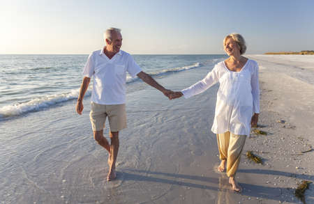 Happy senior man and woman couple walking and holding hands on a deserted tropical beach with bright clear blue skyの写真素材