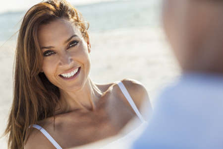 Beautiful smiling middle aged woman with man couple together in sunshine on a beautiful tropical beach