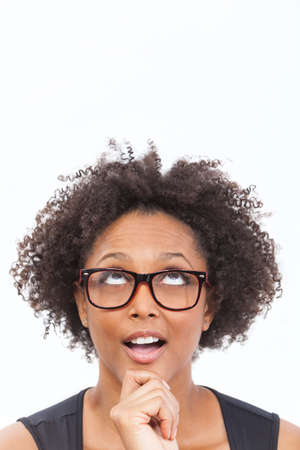 A beautiful intelligent mixed race African American girl or young woman looking up happy thoughtful surprised and wearing geek glassesの写真素材