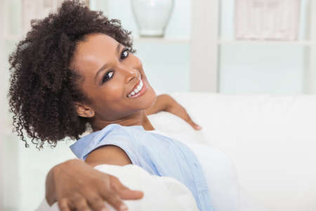 Photo pour A beautiful mixed race African American girl or young woman sitting on sofa at home looking happy and relaxed - image libre de droit