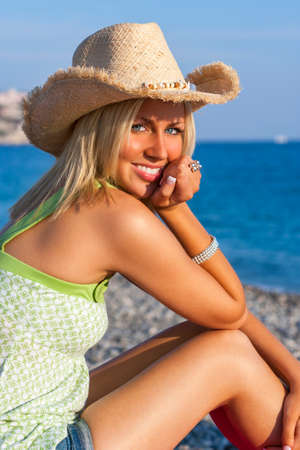 Photo pour Beautiful blond young woman or girl in her twenties happy smiling wearing straw cowboy hat sitting on a beach with blue sea - image libre de droit