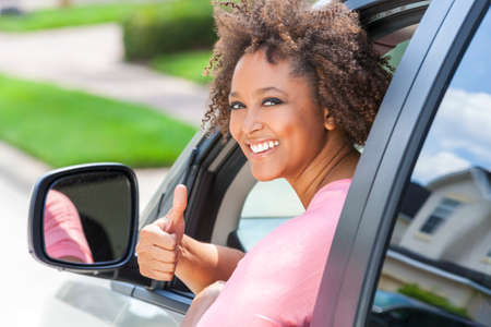 Beautiful young mixed race black African American woman giving thumbs up and driving a car