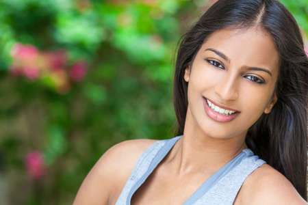 Outdoor portrait of a beautiful Indian Asian young woman or girl outside in summer sunshine with perfect teeth and long hair