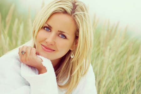 photograph of a beautiful blond haired blue eyed girl or young woman wearing a white towelling robe sitting in tall grass