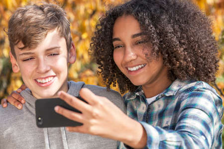 Mixed race group of two happy children teenagers, African American girl caucasian boy laughing together and taking selfie photograph on cell phone smartphone