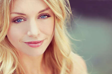 portrait of naturally beautiful woman in her twenties with blond hair and blue eyes, shot outside in natural sunlight