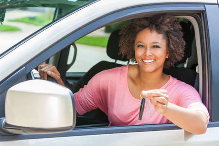 Photo pour Beautiful young mixed race black African American woman driving a car and holding the key - image libre de droit