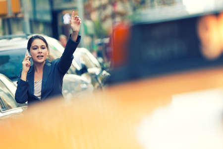 A young woman or businesswoman hailing a yellow taxi cab while talking on her cell phone in a New York City