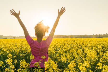 Photo pour Mixed race African American girl female young woman athlete runner teenager in golden sunset or sunrise arms raised celebrating in field of yellow flowers - image libre de droit