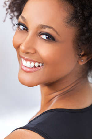 Photo for A beautiful mixed race African American girl or young woman looking happy and smiling with perfect teeth - Royalty Free Image