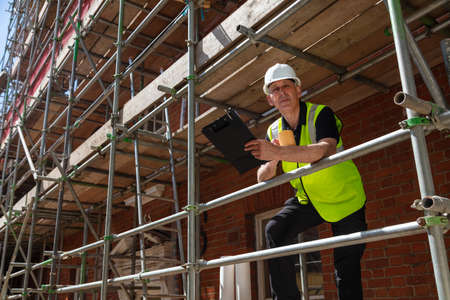 Photo pour Male builder foreman, construction worker, surveyor or architect on site holding a clipboard and drinking a mug of coffee or tea - image libre de droit