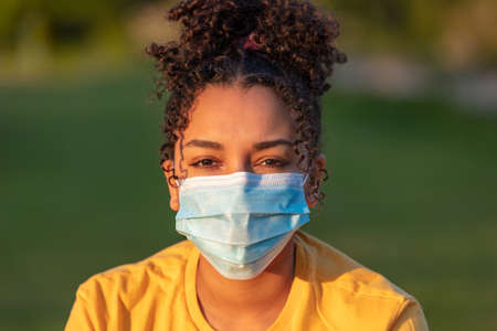Photo pour Mixed race African American teenager teen girl young woman wearing a face mask outside during the Coronavirus COVID-19 pandemic - image libre de droit