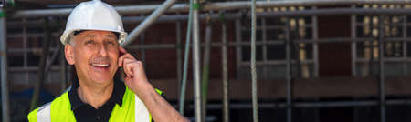Photo pour Panoramic web banner male builder, construction worker, contractor or architect on building site talking on his cell phone panoramic header - image libre de droit