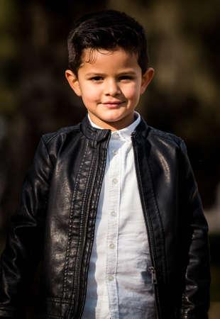 Foto de Fashion little boy wearing a leather jacket. Park or forest, outdoor - Imagen libre de derechos