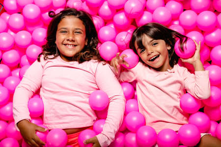 Photo for two little girls smiling and playing at pink ball pool - Royalty Free Image