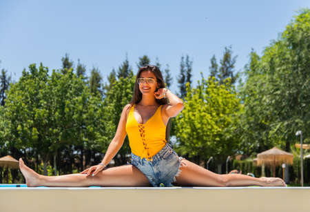 Photo pour Girl stretching by the pool, spread her legs - image libre de droit