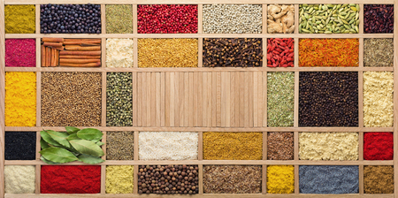 Foto de Spices and herbs in  wooden box, top view. Seasonings from all over the world for cooking food. - Imagen libre de derechos