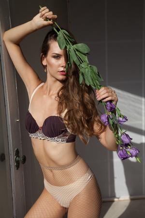 Foto de Portrait of beautiful woman in underwear with flowers - Imagen libre de derechos