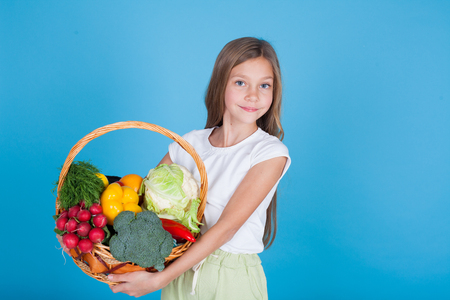 beautiful girl with a basket of fresh vegetables, radishes, broccoli, tomato pepper