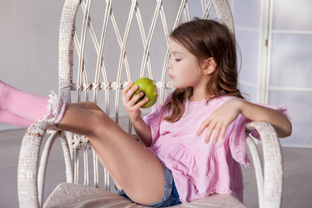 Foto per small beautiful girl eating fresh fruit Green Apple - Immagine Royalty Free