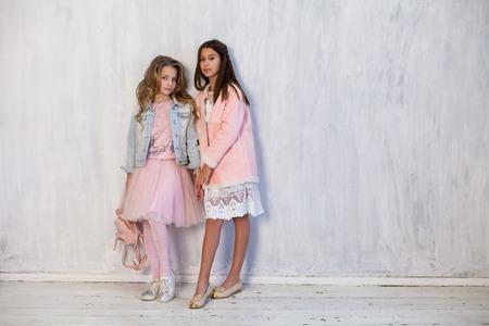 Photo pour two fashionable girls girlfriend in school uniforms - image libre de droit