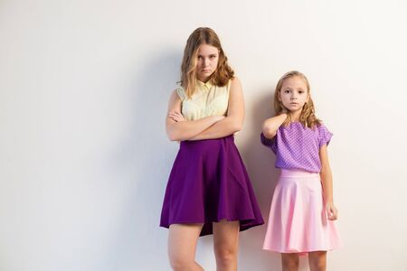 Photo for Portrait of two beautiful fashionable sisters girls on a white background - Royalty Free Image