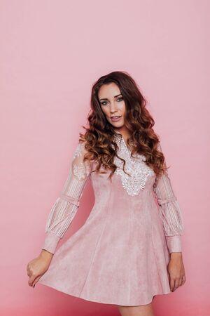 Photo pour Portrait of a beautiful fashionable woman with curls in a pink dress - image libre de droit
