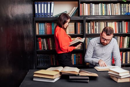 Photo pour a man with a woman in the library prepared for the exam read books 1 - image libre de droit
