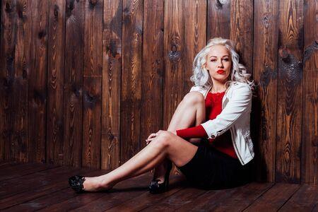 Foto de blonde girl with red lips is a wooden wall - Imagen libre de derechos