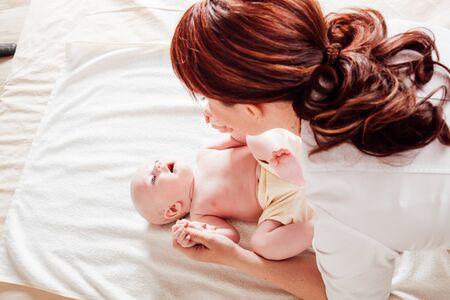 Photo pour the little boy baby mother doing massage hands and legs 1 - image libre de droit
