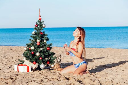 Photo for girl in a bathing suit on a beach new years Eve in the tropics - Royalty Free Image