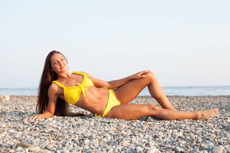 Photo pour Beautiful woman with long hair in yellow swimsuit sunbathes on the beach by the sea - image libre de droit