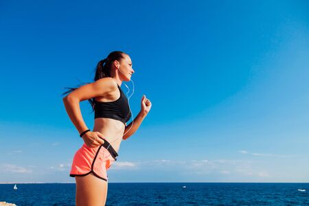 Photo pour woman on the run sports runs on the beach listening to music - image libre de droit