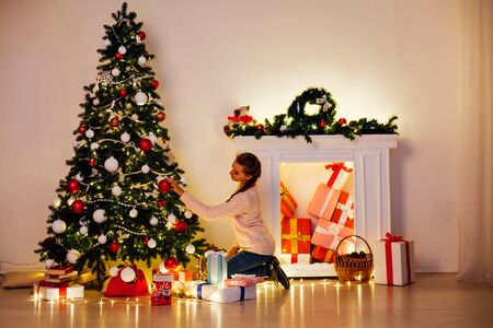 Photo pour beautiful woman decorates the Christmas tree Garland lights new year holiday - image libre de droit
