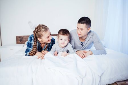 Photo pour mom dad and young son sleep on the bed in the bedroom - image libre de droit