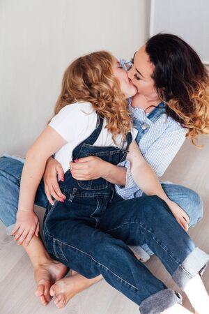 Foto de Mom and daughter in jeans sit together cuddling kisses - Imagen libre de derechos
