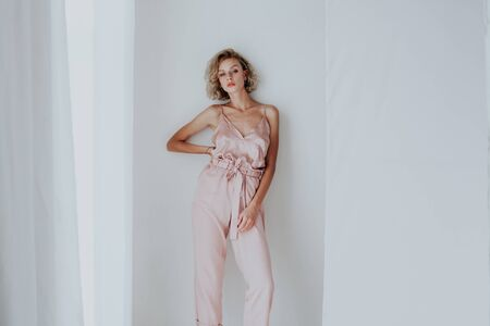 Photo for Beautiful fashionable blonde woman in pink clothes poses in white room - Royalty Free Image