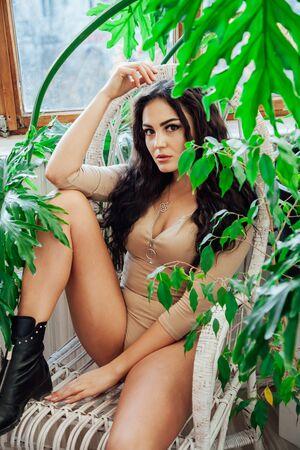Foto de Portrait of a beautiful fashionable brunette woman in beige body shirt also - Imagen libre de derechos